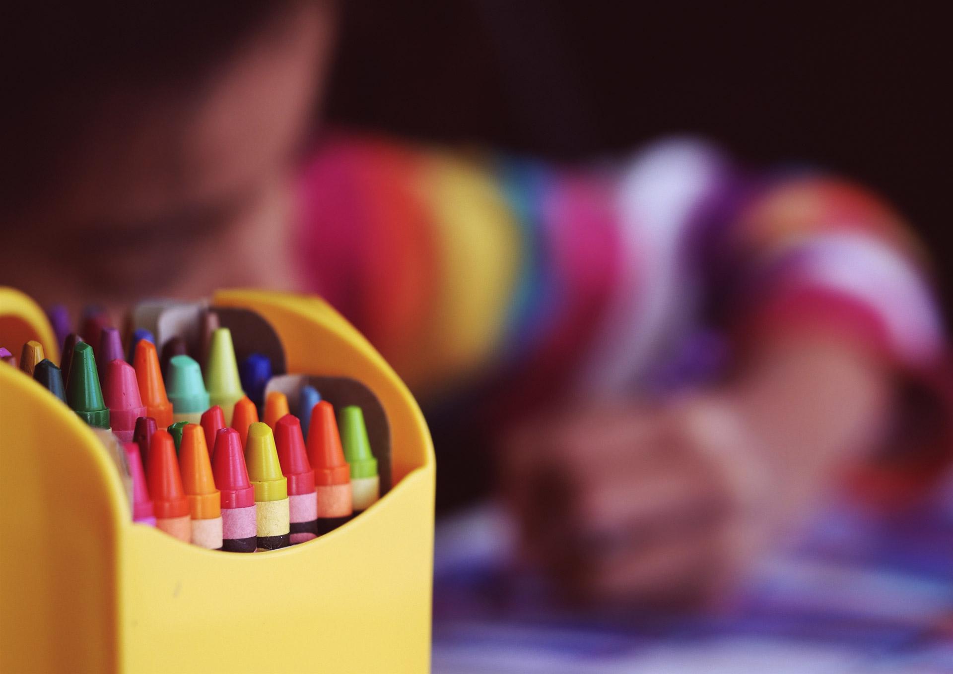 Bambino disegna con tempere colorate.