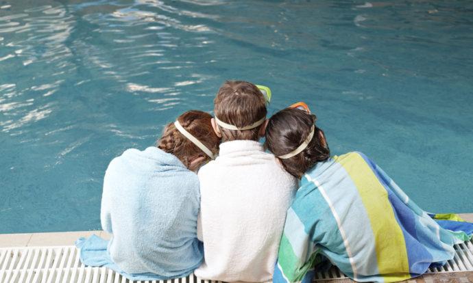 vista da dietro di 3 bambini seduti sul bordo di una piscina